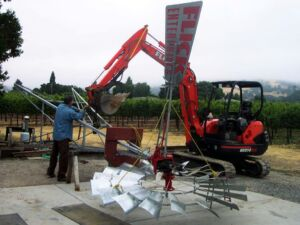 installing windmill with backhoe
